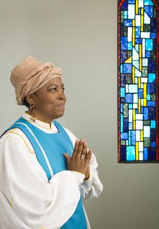 faithfulness: African woman wearing church choir gown and praying