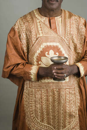 challis: African man wearing traditional dress and holding chalice