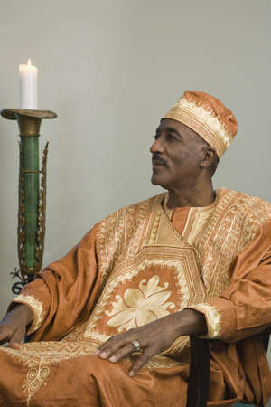 African man wearing traditional dress sitting next to lit candle Stock Photo - 16091820