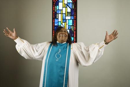 アフリカの女性の身に着けている教会の聖歌隊ガウンと歌