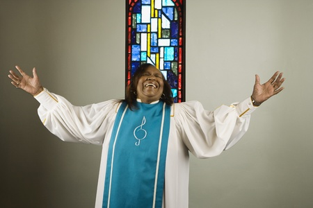 African woman wearing church choir gown and singing 스톡 콘텐츠