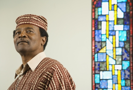 Middle-aged African man next to stained glass window