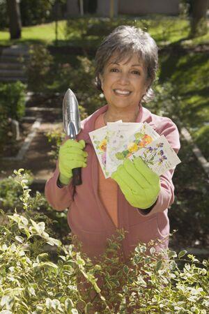 Senior Hispanic woman holding packets of flower seeds Stock Photo - 16091828