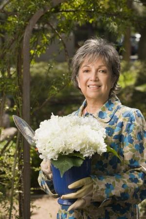 De hogere Spaanse vrouw die potplant buitenshuis