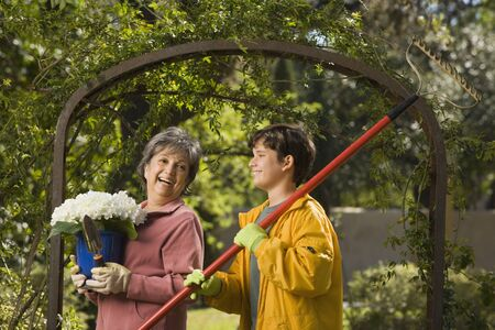 Grandmother and grandson with potted plant and rake