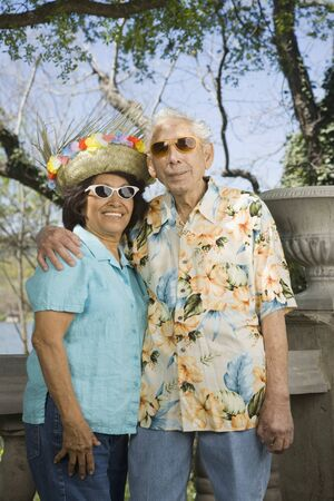 vacationing: Senior couple wearing sunglasses, straw hat and Hawaiian shirt LANG_EVOIMAGES
