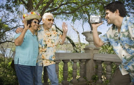 Young man using video camera to film senior couple waving Stock Photo - 16091837