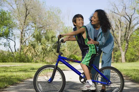 instructing: Hispanic mother smiling at son on bicycle