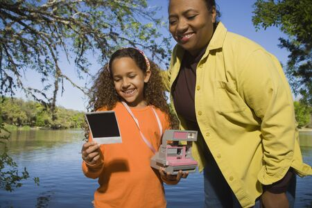 babyboomer: African mother and daughter looking at photograph outdoors