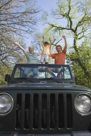 Grandparents and grandson standing in jeep with arms raised