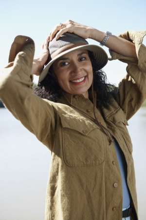 lighthearted: Hispanic woman smiling with hands on head outdoors