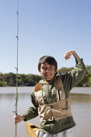 gaithersburg: Hispanic boy holding fishing pole outdoors LANG_EVOIMAGES