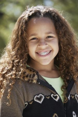 Afrikaans meisje met beugels lachend buitenshuis