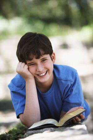 Boy smiling with book outdoors