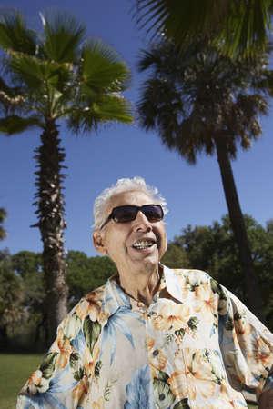 vacationing: Senior man wearing sunglasses and Hawaiian shirt outdoors LANG_EVOIMAGES