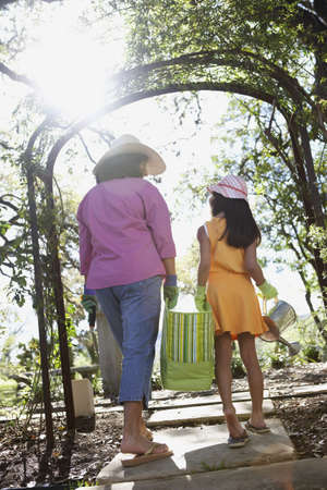 people helping: Mother and daughter carrying gardening supplies outdoors LANG_EVOIMAGES