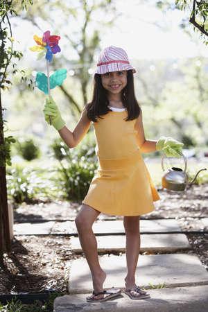 Hispanic girl holding flower pinwheel and watering can outdoors Stock Photo - 16091868