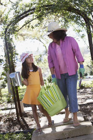babyboomer: Mother and daughter carrying gardening supplies outdoors LANG_EVOIMAGES