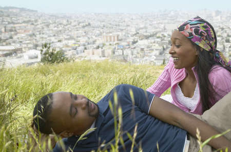 African couple sitting in grass on hill above city Stock Photo - 16091880