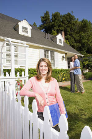 Couple hugging in front of house with real estate agent Stock Photo - 16091884