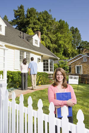 Couple looking at house with real estate agent Stock Photo - 16091885