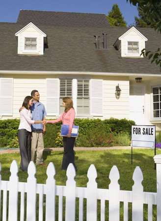 flogging: Couple shaking hands with real estate agent