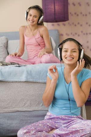Hispanic sisters listening to music on headphones Stock Photo - 16091904