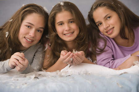 3 persons only: Hispanic sisters laying on bed with down feathers