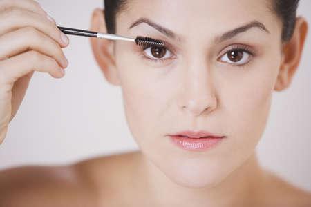 Close up studio shot of Hispanic woman applying mascara Stock Photo - 16091912