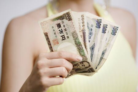 south western european descent: Close up of woman holding fanned out money LANG_EVOIMAGES