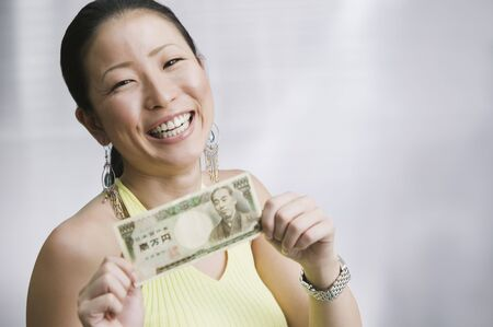 relishing: Close up of Asian woman holding money LANG_EVOIMAGES