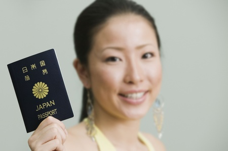 south western european descent: Asian woman smiling and holding passport