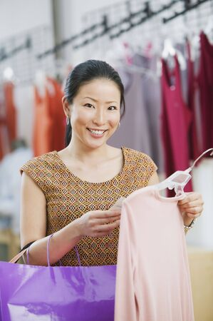 Asian woman looking at price of shirt at boutique Stock Photo - 16091928
