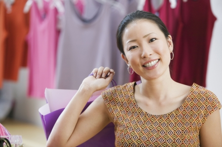 south western european descent: Asian woman smiling and holding shopping bag
