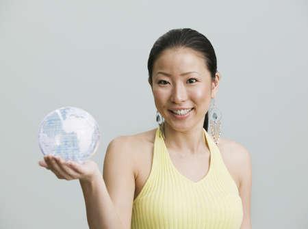 appendage: Studio shot of Asian woman holding globe LANG_EVOIMAGES