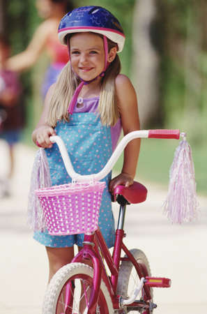 facing away: Young girl holding bicycle with tassels and basket