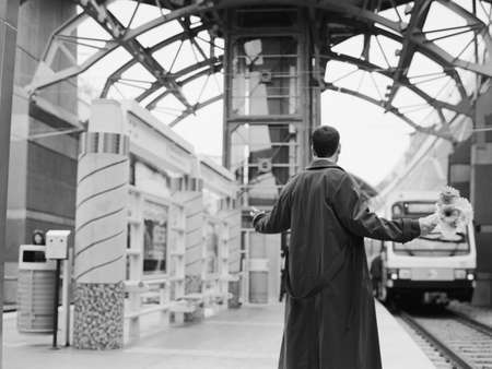 Man holding flowers with arms out at train station Stock Photo - 16091937