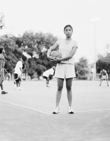 Asian girl holding basketball on court Stock Photo - 16091943