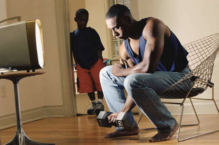 African man lifting dumbbell while son watches Stock Photo - 16091944
