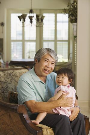 Asian grandfather holding young granddaughter on lap