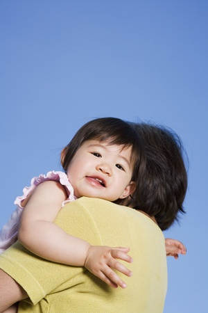 Asian baby looking over mothers shoulder