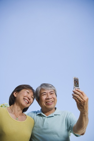 south asian: Senior Asian couple taking own photograph with cell phone