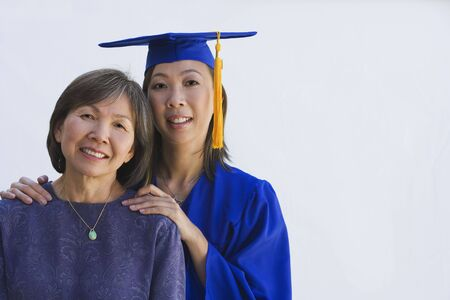 graduating seniors: Asian woman in graduation cap and gown with mother LANG_EVOIMAGES