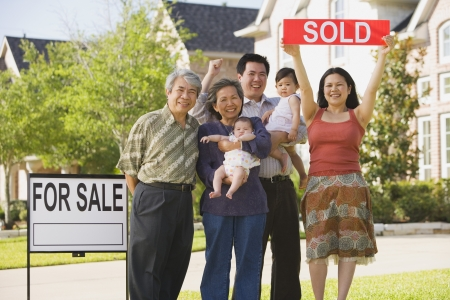 Multi-generational Asian family holding up Sold sign in front of house LANG_EVOIMAGES