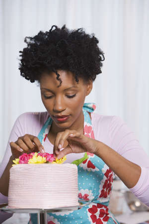 seriousness skill: Young African woman putting flowers on cake LANG_EVOIMAGES