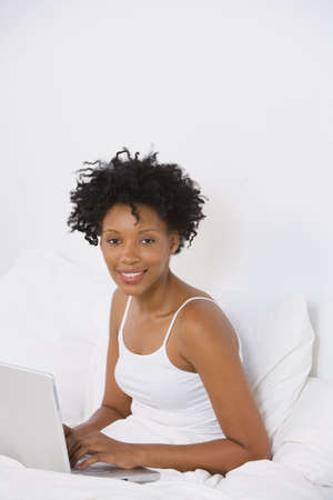 Young African woman using laptop in bed Stock Photo - 16091968