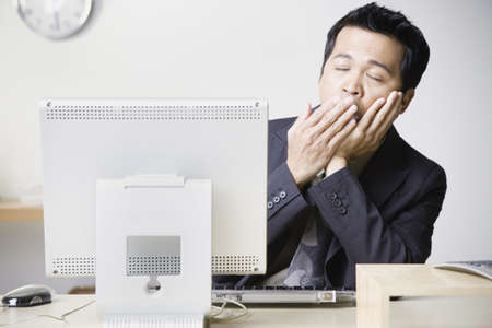 wearying: Asian businessman sitting at computer yawning