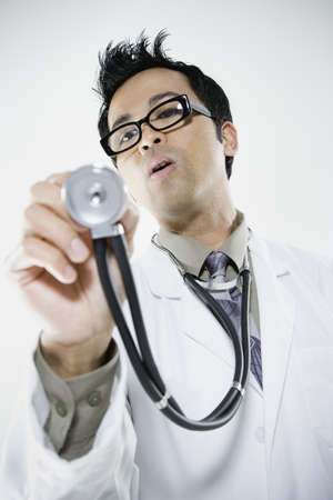 Asian male doctor holding out stethoscope Stock Photo - 16091977