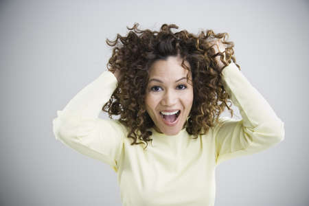mischievious: Woman smiling and grabbing her hair LANG_EVOIMAGES