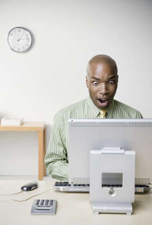 reacting: African businessman working at desk